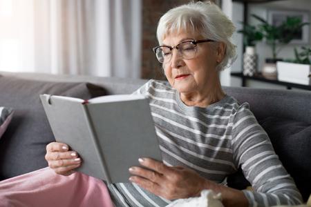 Interesante jubilación. Retrato del libro de lectura envejecido de la mujer curiosa. Ella está sosteniendo el volumen mientras se relaja en un cómodo sofá con almohadas suaves