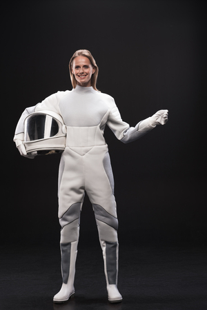 Full-length portrait of optimistic young charming lady cosmonaut is standing in protective suit and holding helmet while gesturing like holding something. She is looking at camera with joy. Isolated
