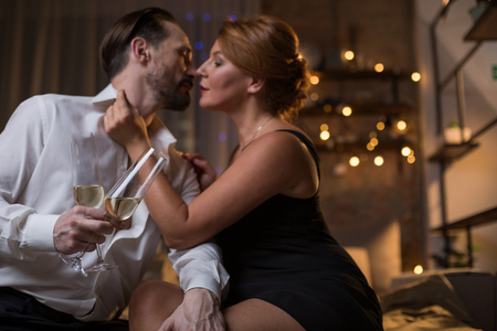 Impulse of passion. Sensual loving couple is kissing in bedroom while celebrating their anniversary. Man is holding two glasses of alcohol beverage Stock Photo