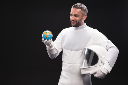 My home. Happy young unshaven cosmonaut wearing hyperbaric protective suit is standing and holding helmet and small globe of earth. He is looking at it curiously. Isolated background Stock Photo