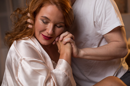 I am so happy with you. Portrait of glad red-haired woman holding male hand with love. Her eyes are closed with enjoyment while man is embracing her