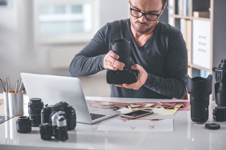 심각한 unshaven 남자 사무실에서 책상에 situating 동안 카메라에 렌즈 시스템을 설정합니다. 직업 개념 스톡 콘텐츠