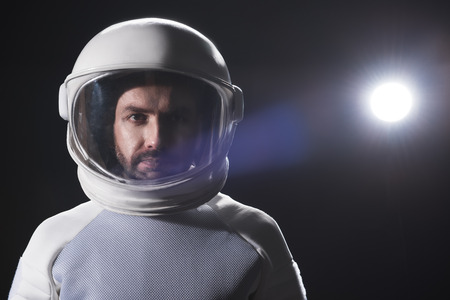 Sense of responsibility. Portrait of serious bearded astronaut wearing helmet and hyperbaric protective costume is standing and looking at camera confidently. Black background with copy space