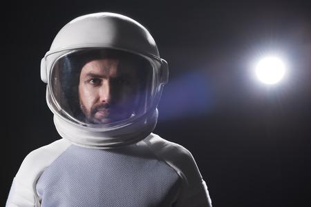 Senso di responsabilità. Il ritratto dell'astronauta barbuto serio che indossa il casco e il costume protettivo iperbarico è in piedi e guarda con fiducia la fotocamera. Sfondo nero con spazio di copia Archivio Fotografico - 91857995