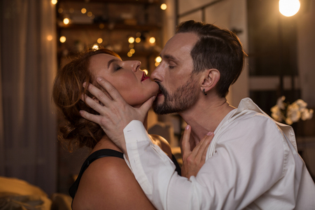 Profile of passionate bearded man kissing woman with desire while touching her face gently. Female eyes are closed with pleasure. Closeness concept Stock Photo
