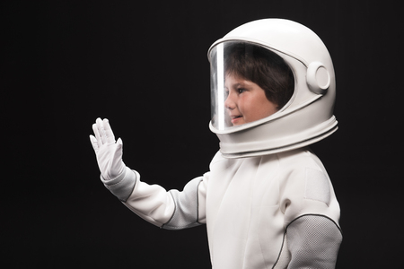 Hi. Side view of amiable little spaceman is standing in helmet with full armor and waving to somebody. He is expressing interest and friendliness. Isolated background