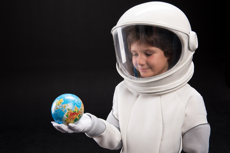 My land. Waist up of little cosmonaut wearing helmet and protective suit is standing and holding small model of earth while expressing interest. Isolated background and copy space in the left side