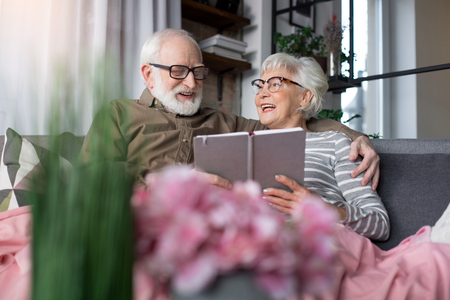 Pleasant memories. Portrait of old charming couple remembering sweet moments. Woman is looking at husband while laughing. Man is regarding at picture while tenderly cuddling wife Stock Photo
