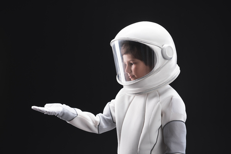Never see this before. Side view profile of pleasant astronaut is standing in helmet with full armor and holding hand palm up. He is looking at it with interest and concentration. Isolated background Stock Photo