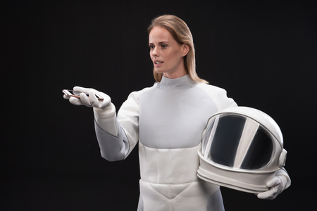 No connection. Serious young spacewoman is standing in protective suit while holding helmet and smartphone. She is looking at screen of gadget while expressing disappointment. Isolated