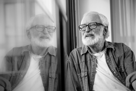 Black-and-white portrait of wrinkled bearded positive pensioner observing life at the street