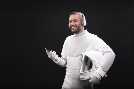 Best music. Joyful bristled spaceman in headphones is listening to song using smartphone while standing with closed eyes. He is wearing protective suit and holding helmet. Isolated with copy space