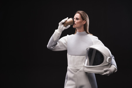 Coffee time. Elegant female astronaut is drinking espresso while standing in protective costume and holding white helmet. She is looking aside thoughtfully. Isolated background with copy space
