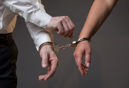 Sending you free. Close up of male hand unlocking female one from joint handcuffs by key. Divorce concept. Isolated