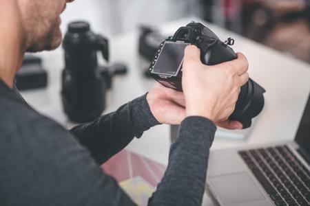 トップビューは、写真を撮るためのデジタルデバイスを保持している男性の手をクローズアップします。彼は机の上でスクリーンを見ている。イメ