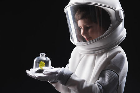 Discovering new life. Side view of concentrated child cosmonaut wearing helmet and specialized protective costume is standing and holding green plant in palm while expressing curiosity. Isolated