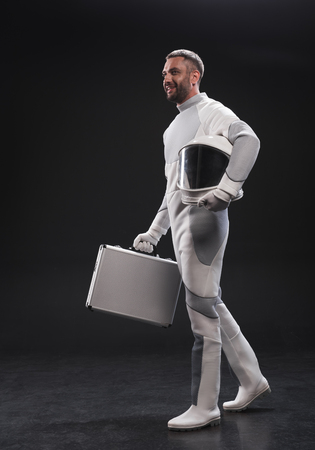 Important appointment. Full-length of cheerful bearded astronaut in protective suit is standing with helmet and carrying his suitcase while looking aside with smile. Business in space concept Stock Photo