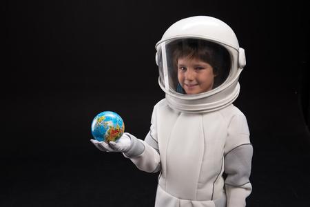 La mia patria. Mezzo busto ritratto di ragazzo ottimista astronauta che indossa il casco è in piedi e in possesso di un piccolo globo di terra mentre guardando la fotocamera con gioia. Spazio isolato della copia e della priorità bassa Archivio Fotografico - 91858053