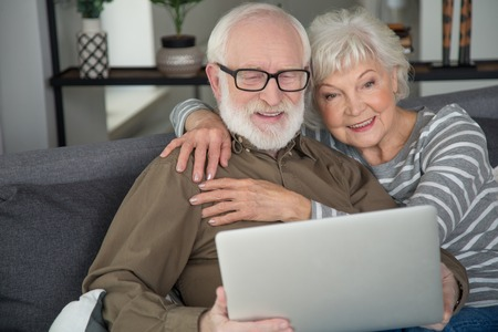 Holiday together. Portrait of old couple watching laptop while sitting at living room. Woman is tenderly hugging man while they are smiling Stock Photo