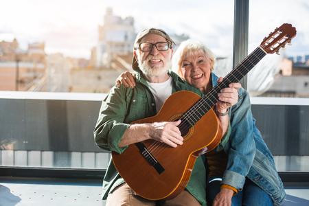 若さを覚えてください。魅力的な既婚の年配の男性と女性の楽器の演奏を楽しんでします。夫は舌を出している間、彼らはカメラを見ています。コ 写真素材