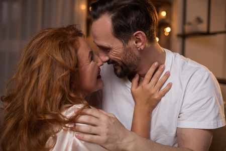 Profile of excited man and woman touching noses with joy. They are cuddling and smiling Stock Photo