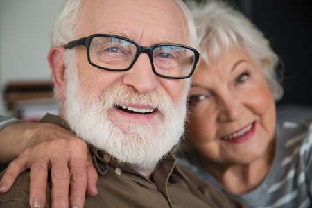 Happy retirement. Close up portrait of excited mature man and woman smiling while resting at home. Focus on male while they are bonding to each other