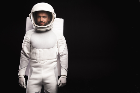 Ready for new discovery. Portrait of concentrated young cosmonaut wearing hyperbaric astronaut protective suit is standing and looking at camera confidently. Isolated background with copy space