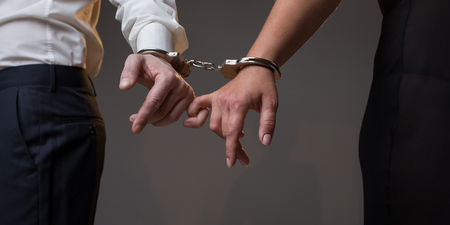 Close up of man and woman arms tied with manacles. They are holding fingers together. Loving connection concept. Isolated 写真素材
