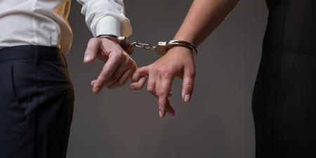 Nahaufnahme von Mann und Frau Arme mit Handschellen gebunden. Sie halten die Finger zusammen. Liebevolles Anschlusskonzept. Isoliert