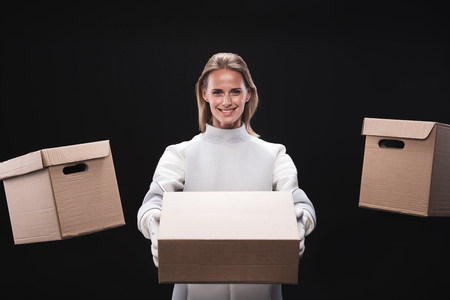 Lets move. Portrait of optimistic nice spacewoman wearing protective costume is standing with boxes on sides and holding carton while looking at camera with smile. Isolated. Resettlement concept
