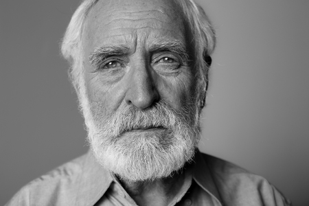 Close up black-and-white portrait of sorrowful man looking at camera while standing. Isolated on grey background Stockfoto