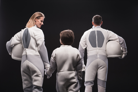 Harmonious relations. Back view of positive astronaut mother is holding by hand her little son while standing together with father. Isolated background. Migration concept Фото со стока