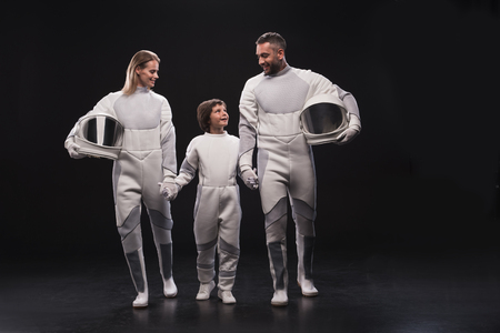 Together everywhere. Full-length of cheerful family of cosmonauts are standing together with helmet while holding by hands and looking at each other with joy. Resettlement concept. Dark background