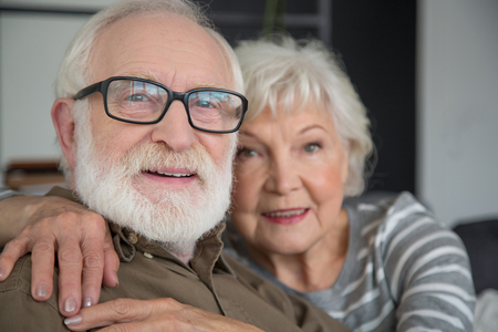 Portrait of curious old couple embracing each other. Focus on male while they are smiling and watching with interest