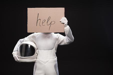 In cerca di supporto. La donna che indossa la tuta protettiva per astronauta iperbarica è in piedi e in possesso di casco. Si copre il viso con l'aiuto di cartone. Concetto di pericolo. Isolato con spazio di copia Archivio Fotografico - 91858090