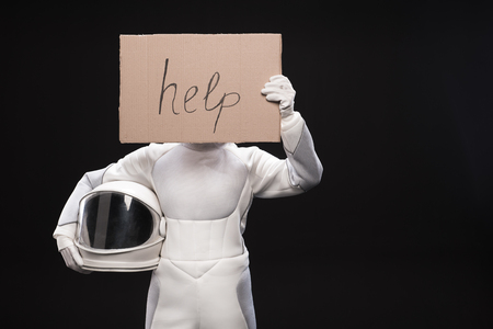 Seeking support. Woman wearing hyperbaric astronaut protective suit is standing and holding helmet. She is covering her face with cardboard help. Danger concept. Isolated with copy space