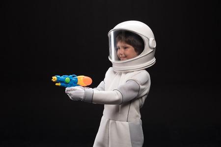 Guardia. Il piccolo astronauta allegro in casco sta stando e tenendo la pistola del giocattolo in sue mani mentre mira con il sorriso. Sta proteggendo la sua terra. Sfondo isolato Archivio Fotografico - 91858095