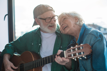 Favorite song. Portrait of two happy pensioners looking to each other with love. Man is playing on musical instrument