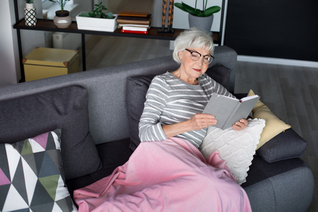 Portrait of old mature interested lady lying on couch at cozy home. She is wisely looking in book while legs are covered with soft blanket. Copy space in left side