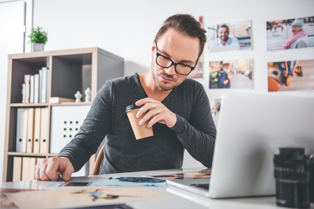 Portrait of serene bearded man looking at different photos while drinking mug of appetizing beverage in room. Occupation concept Stock Photo