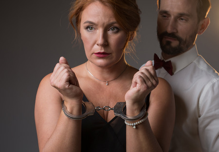 I am your prisoner. Portrait of frustrated middle-aged woman showing her hands locked by handcuffs. Man is standing near her and looking at lady with confidence. Isolated Foto de archivo