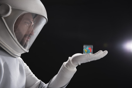 Side view profile of serious trained spaceman wearing helmet and protective costume is standing and looking at his palm with small cube with globe. Close-up of male arm. Black background Stock Photo