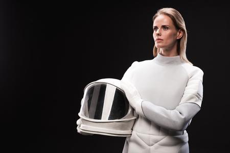L'astronauta della giovane signora che porta il costume protettivo è in piedi e guarda malinconicamente mentre tiene il casco. Sfondo isolato con spazio di copia nella parte sinistra. Concetto di cosmo Archivio Fotografico - 91858113