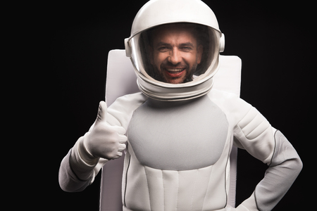 I am ok. Waist up portrait of cheerful spaceman wearing helmet with full armor is standing and looking at camera with joy while showing thumb-up. Isolated background. Cosmonaut concept Фото со стока