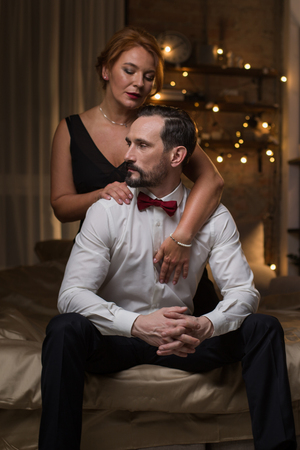 Full length portrait of passionate loving couple sitting on bed at night. Elegant lady is embracing husband from behind