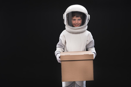 Ik ben klaar. Het portret van vrolijk weinig ruimtevaarder die helm en beschermend kostuum draagt bevindt zich en houdt doos terwijl het bekijken camera met glimlach. Geïsoleerd met kopie ruimte. Hervestiging concept Stockfoto