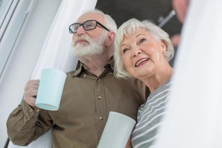 白いカーテンから2人の幸せな老男女の低角が現れています。彼らは笑っておいしいホットドリンクを楽しんでいます 写真素材 - 91858126