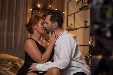 情熱的な愛情のあるカップルは、寝室で欲望とキスし、抱きしめています。カメラは彼らの親密さを記録しています 写真素材