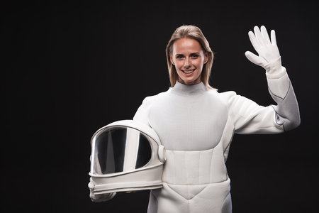 Hello. Portrait of friendly young attractive spacewoman is standing in full armor and holding helmet while waving her hand. She is looking at camera with smile. Isolated with copy space Фото со стока - 91858133
