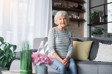 Portrait of mature woman resting on comfortable couch at home. She is smiling and looking at camera